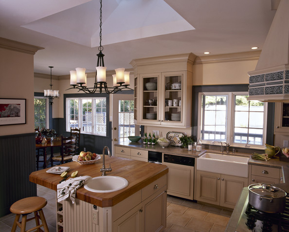 A beautiful kitchen with low wood table, chairs, and island.