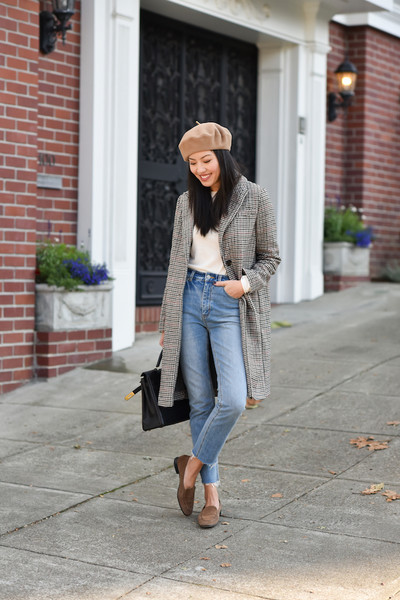 In a neutral color with a plaid coat, blue jeans and loafers.