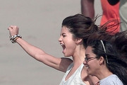 Selena Gomez, joined by a host of young girls, shoots a music video for her upcoming single at a Los Angeles beach. In between takes, Selena could be seen bundling up in a robe and getting a hug from a friend.
